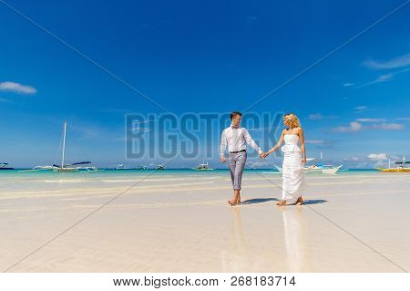 Happy Bride And Groom Having Fun On The Tropical Beach. Tropical Sea And Palm Boats In The Backgroun