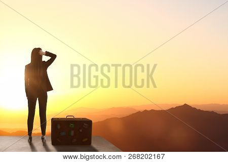 Back View Of Backlit Woman Standing On Rooftop With Luggage And Beautiful Landscape View. Vacation A