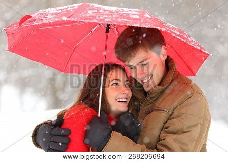 Romantic Couple Hugging Under An Umbrella Snowing In Winter Holiday
