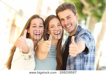 Front View Portrait Of Three Happy Friends Smiling With Thumbs Up In The Street
