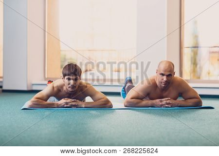 Two Sporty Men Rest After Doing The Exercise. Men Lie On A Mat After A Good Physical Exercise The Gy