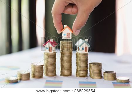 Woman Hand Hold A  Home Model Put On The Stack Coin With Growing, Savings Money For Buy House And Lo