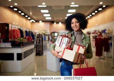African American Girl Shopping Gifts In Mall On Christmas Sale. New Year Holidays Concept. Smiling A