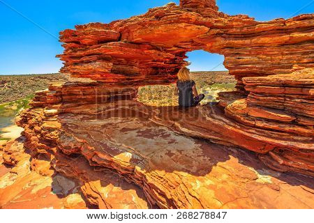 Blonde Caucasian Woman Sitting Inside The Iconic Rock Arch In Red Sandstone Of Natures Window, Kalba