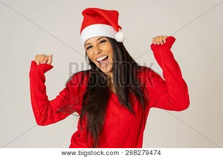 Attractive Sexy Girl Posing In Red Dress And Santa Hat Isolated On Grey Background