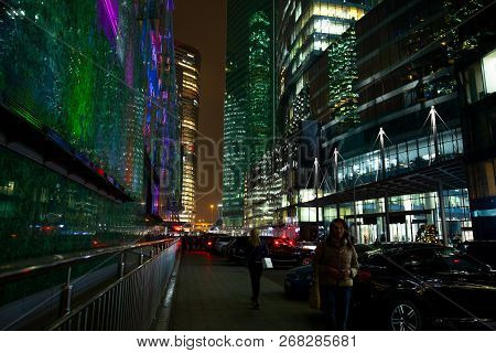 The Sidewalk On A Busy Street Of The City And Passersby People. Business Center And Skyscrapers Of A