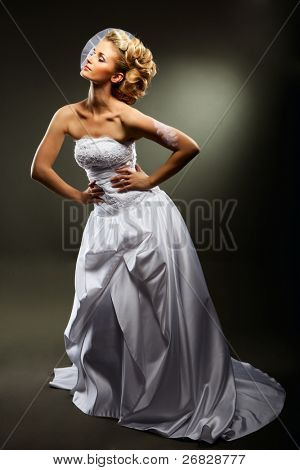 beautiful girl wearing luxurious wedding dress over studio background