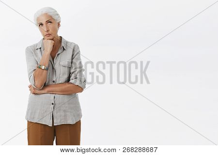 Portrait Of Intense Serious-looking Concerned Old Woman Holding Fist Above Chin Looking Up Standing