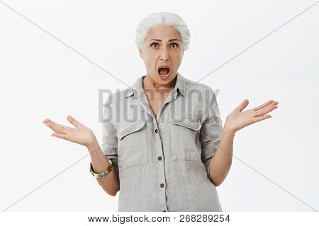 Studio Shot Of Confused And Displeased Shocked Senior Mother With White Hair Shrugging Raising Palms