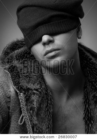 Close-up portrait of handsome young man wearing in a fur jacket and knitted hat (b&w)