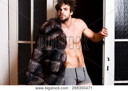 Guy Attractive Posing Fur Coat On Naked Body. Richness And Luxury Concept. Luxury Lifestyle And Well