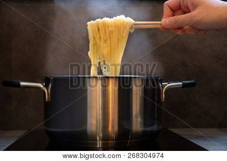 Hand Holding Wooden Chopsticks Of Instant Noodles Or Ramen With Smoke.steam From Hot Soup Bowl Selec