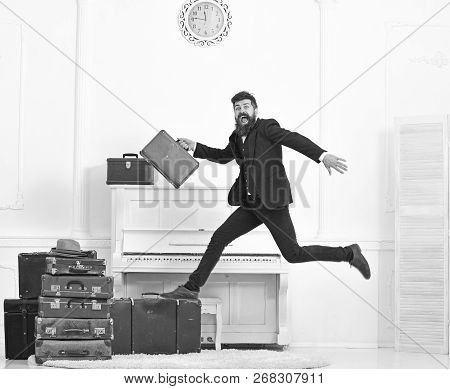 Macho attractive, elegant on cheerful face carries vintage suitcases, jumping. Man with beard and mustache in suit carries luggage, luxury white interior background. Long awaited vacation concept poster
