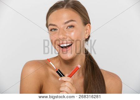 Portrait of a smiling young topless woman isolated over white background, holding lip gloss poster