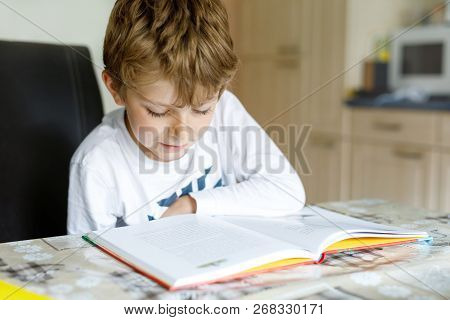 Little Blonde School Kid Boy Reading A Book At Home. Child Interested In Reading Magazine For Kids.