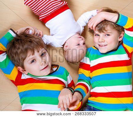 Two Happy Little Preschool Kids Boys With Newborn Baby Girl, Cute Sister. Siblings, Twins Children A