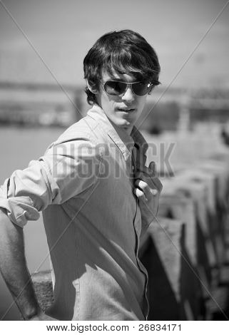 Portrait of handsome young man with wearing sunglasses outdoors (black and white)