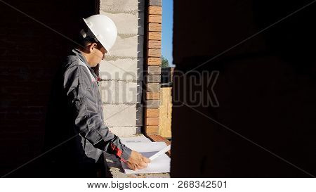 Side view of man in hardhat standing at window in house under construction looking at paper draft poster