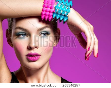 Fashion portrait of a beautiful woman with bright makeup. Closeup face of a beautiful fashion model. Gorgeous face of an attractive girl Portrait of a girl with bracelets  thorns.