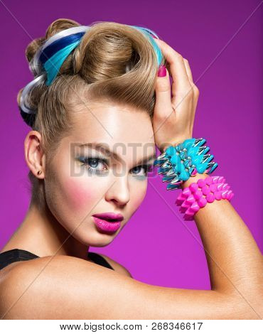 Fashion portrait of young caucasian model with bright makeup. Beautiful woman with creative hairstyle. woman with  Fashion make-up - pink background. Portrait of a girl with bracelets on her hands