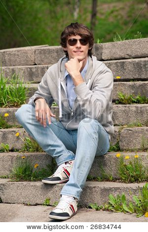 Portrait of handsome young man wearing sunglasses sitting on stairway in park