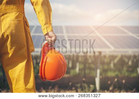 Electrical Worker Or Engineer Holding Safety Hat Stand At Power Plant.foreman Wearing Orange Safety