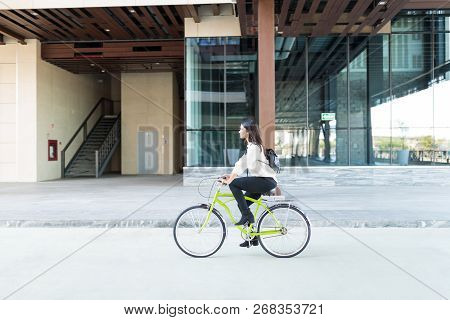 Female Environmentalist Riding Bicycle On Street Against Office Building