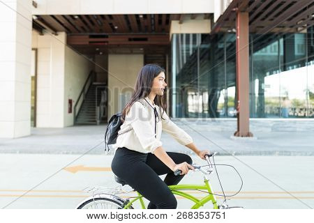 Responsible Businesswoman Commuting By Bicycle To Work Against Building