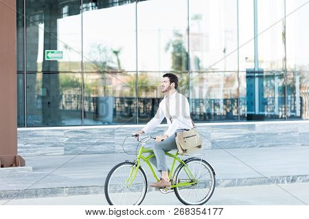 Full Length Of Confident Sales Executive Riding Cycle And Living Eco-friendly Lifestyle
