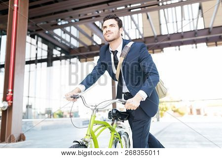Determined Manager In Elegant Suit Riding Vintage Bicycle In City