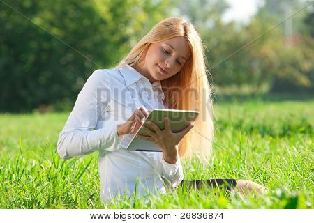 Young  business woman sitting on grass and using electronic tablet outdoors