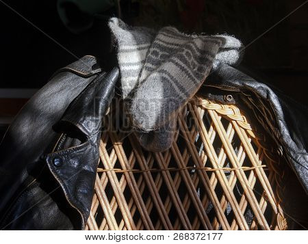 Wool Socks And Leather Jacket Hanging On A Chair