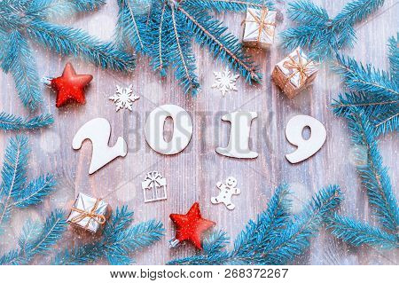 New Year 2019 background with 2019 figures, Christmas toys, blue fir tree branches and snowflakes. New Year 2019 festive season still life, 2019 New Year composition