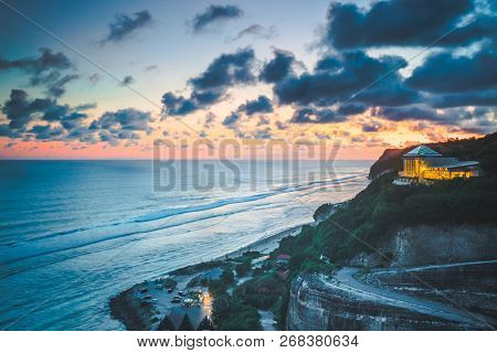 Overview ocean, cliff, hotel. Sunset landscape, Bali. Gorgeous scenery the colorful sunset cloudy sky over the ocean and steep cliff with luxury hotel. Perfect mix of the dark blue and orange colors.