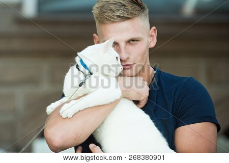 He Is More Than Just A Pet. Happy Cat Owner With Muscular Look. Cat Relaxes In Arms Of His Owner. Ha