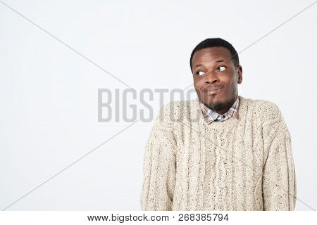 Doubtful African Man In Sweater Shrugs Shoulders