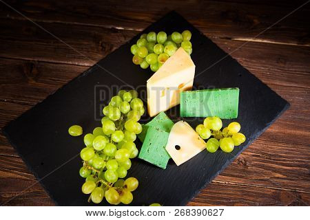 Various Types Of Cheese With Green Grapes On Black Slate Cheeseboard On Table
