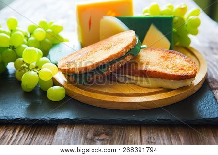 Two Hot Grilled Or Fried Sandwich With Cheese And Green Grapes On Black Slate Cheeseboard On Wooden