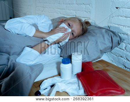 Little Girl Lying Sick In Bed Blowing Her Nose Feeling Sick With High Fever Having A Cold Flu