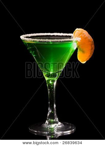 Back lit martini glass with absinthe cocktail decorated by salt rim and tangerine slice