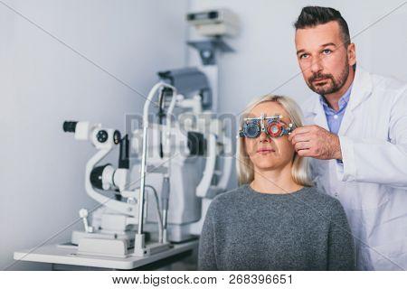 Optician examining woman's eyes. Eyesight diagnostics, medical examination.
