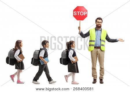 Full length shot of schoolchildren walking in a line and a teacher with a safety vest and stop sign showing way isolated on white background poster