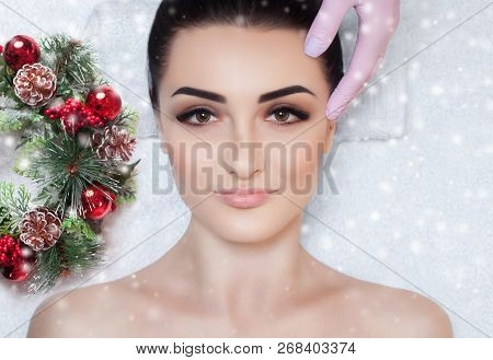 A Beautiful Woman Gets A Facial Massage In The Spa Salon. Closeup Of Woman's Face And New Year Wreat