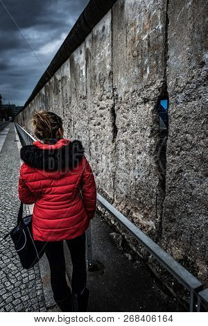 Woman Wearing Red Jacket Visits Remains Of Berlin Wall