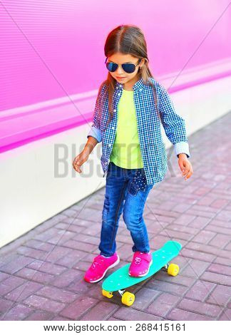 Fashion Child Little Girl On Skateboard On Colorful Pink Wall Background