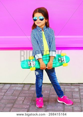 Fashion Child Little Girl With Skateboard On Colorful Pink Wall Background