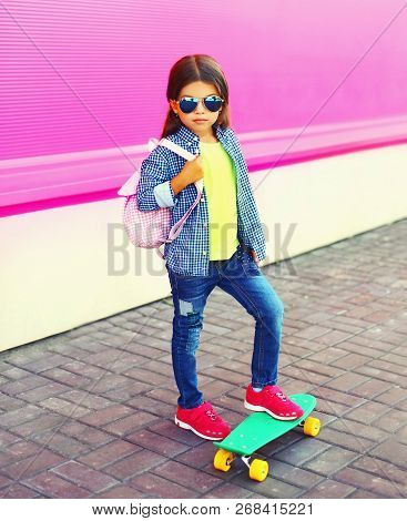 Fashion Little Girl Child With Skateboard, Backpack In City On Colorful Pink Wall Background