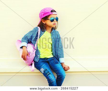 Fashion Little Girl Child Wearing Sunglasses, Baseball Cap, Backpack On City Street On White Backgro