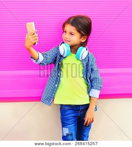 Happy Smiling Child Taking Selfie By Smartphone In City On Colorful Wall Background