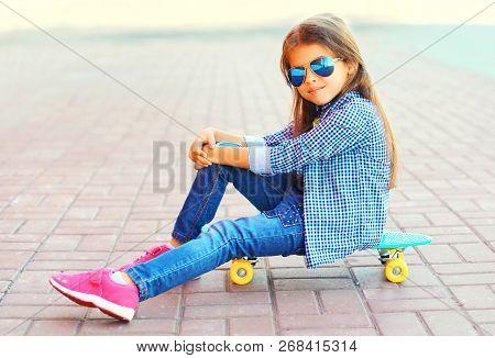 Stylish Little Girl Child Sitting On Skateboard On City Street